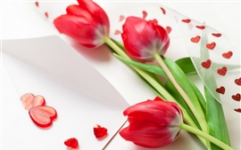 Three red tulip flowers, ribbons, heart-shaped decoration