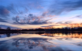Beautiful sunset, calm lake, reflection in the water, shore trees, sky clouds
