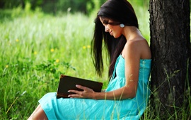 Blue dress girl reading a book under the tree