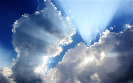 Blue sky, white clouds, sun rays