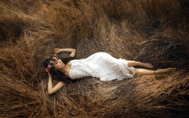 Blanco vestido de niña acostada en el heno