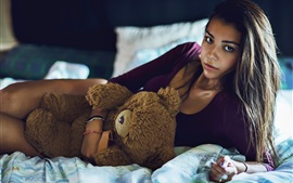 Girl with teddy bear at bed