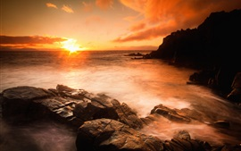 Pôr do sol sobre o mar, praia, rochas, pedras, nuvens