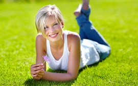 Preview wallpaper Blonde girl, grass, flower, smile