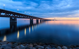 Preview wallpaper Sweden, bridge, lights, beach, stones, evening, sunset, sky, clouds, blue