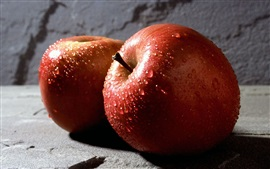 Two red apples, water drops