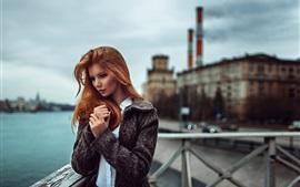 Menina vermelha do cabelo, casaco, cais