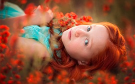 Red hair girl lying in flowers