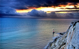Preview wallpaper Sea, rock, lighthouse, sky, clouds, sunset, dusk