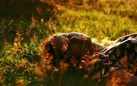 Fille de sommeil dans l'herbe, l'été