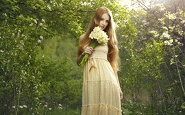Beautiful blonde girl holding a bouquet daffodils flowers