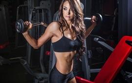 El entrenamiento con pesas, gimnasio, chica pelo rizado