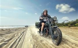 Joven a caballo de la motocicleta en la playa