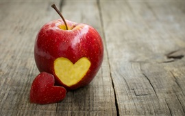 Single red apple, love hearts, wood board