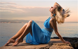 Preview wallpaper Beautiful blue dress girl, sit at seaside, wind