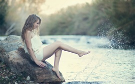 Menina senta-se na pedra para jogar água, respingo