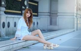 A menina asiática lindo e puro, sentar-se no lado da rua