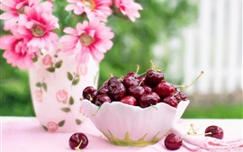 A bowl cherries, pink flowers