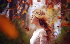 Blonde girl in autumn, leaves flying, wind