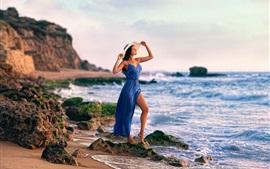 Blue dress girl at coast, rocks, sea