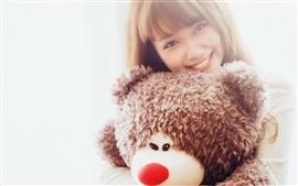 Sorriso asiático da menina e urso de peluche