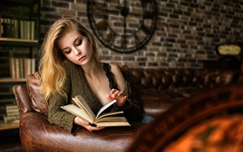Preview wallpaper Blonde girl reading book on sofa