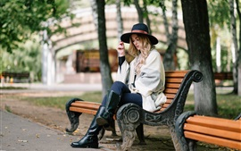 Blonde girl sit on bench