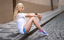 Preview wallpaper Curly haired blonde girl sit at street side, beautiful legs