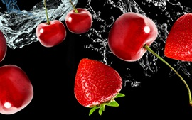 Fresh fruit, cherries and strawberries, water, black background