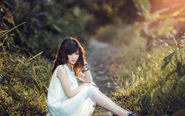 White dress Asian girl sit at ground, grass, sunshine