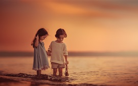 Дети играют в игры на море, закат