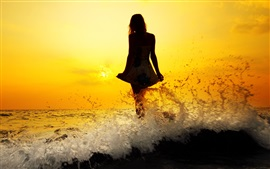 Girl standing at seaside water, waves, splash, silhouette, sunset