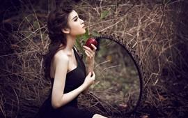 Menina de vestido preto bonito, mãos, maçã