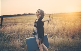 Preview wallpaper Sunset, girl, suitcase, camera, grass