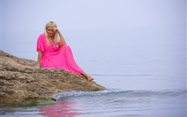 Preview wallpaper Blonde girl, pink dress, sit at lakeside
