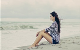 Brunette hair girl sitting at the beach, sea, wind