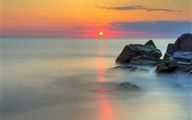 Mar, piedras, cielo rojo, la reflexión del agua, las nubes, la salida del sol