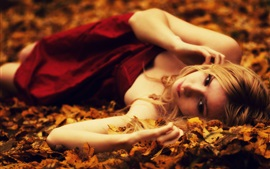 Preview wallpaper Blonde girl lying on the ground, leaves, autumn