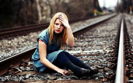Blonde girl sit at railroad