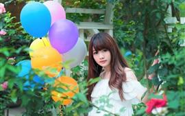 Menina asiática encantadora, balões coloridos