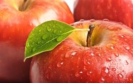 Свежие красные яблоки, капли воды, листья