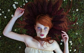 Red hair girl, freckles, lying on flowers