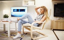 Блондинка сидит на стуле, чтобы отдохнуть