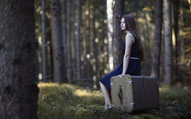Menina de saia azul, cabelos longos, mala, floresta