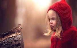 Curious little girl look at frog