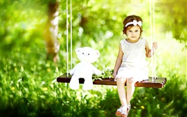 Preview wallpaper Cute little girl and teddy bear sit on swing