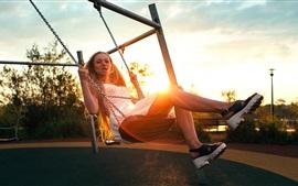 Девочка играет качели, солнце
