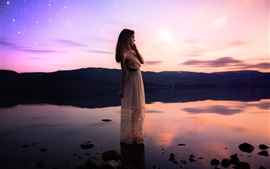 Girl standing at lakeside, water, sunset, stars