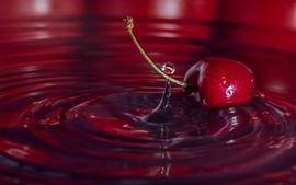 Красная вишня падает на воду