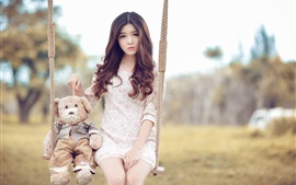 Asian girl and teddy bear sit on swing